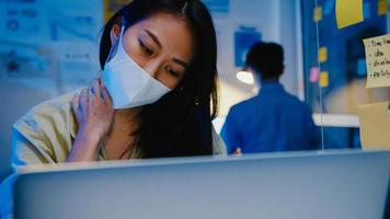gestresste vermoeide jonge aziatische vrouw draagt een gezichtsmasker met behulp van laptop hard werken met kantoorsyndroom, nekpijn, tijdens overuren op kantoor. 's nachts thuiswerken overbelasting, social distancing. foto
