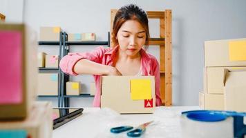 jonge azië ondernemer zakenvrouw verpakking product in kartonnen doos leveren aan klant, werken op kantoor aan huis. eigenaar van een klein bedrijf, start online marktlevering, lifestyle freelance concept. foto