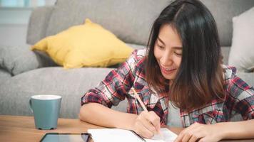 aziatische studentenvrouw doet thuis huiswerk, vrouw gebruikt tablet om thuis op de bank in de woonkamer te zoeken. levensstijl vrouwen ontspannen thuis concept. foto