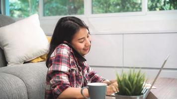 freelance aziatische vrouw die thuis werkt, zakelijke vrouw die op laptop werkt en mobiele telefoon gebruikt om met de klant op de bank in de woonkamer thuis te praten. levensstijl vrouwen die thuis werken concept. foto