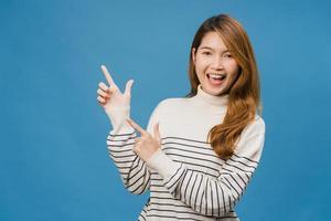 portret van een jonge aziatische dame die lacht met een vrolijke uitdrukking, toont iets geweldigs op lege ruimte in casual kleding en kijkt naar camera geïsoleerd over blauwe achtergrond. gezichtsuitdrukking concept. foto