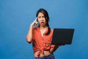 jonge Aziatische dame met behulp van laptop met negatieve uitdrukking, opgewonden schreeuwen, huilen emotioneel boos in casual doek en staan geïsoleerd op blauwe achtergrond met lege kopie ruimte. gezichtsuitdrukking concept. foto