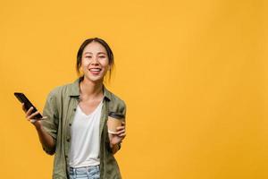 verraste jonge aziatische dame die telefoon gebruikt en koffiekopje vasthoudt met positieve uitdrukking, breed glimlacht, gekleed in casual kleding en kijkt naar camera op gele achtergrond. gezichtsuitdrukking concept. foto