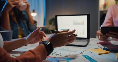 millennial azië mensen strategische vergadering presentatie brainstormen ideeën over nieuw papierwerk project collega's die samenwerken plannen successtrategie genieten van teamwork in een klein modern nachtkantoor. foto