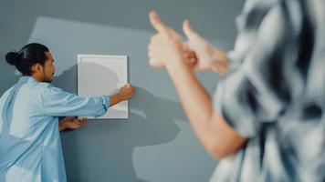 gelukkige Aziatische jonge aantrekkelijke paar man en vrouw helpen elkaar fotolijstje aan de muur te hangen versieren huis en kartonnen doos pakket in de woonkamer. jonge getrouwde Aziatische decoreren huis concept. foto
