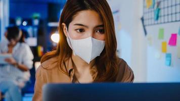gelukkige zakenvrouw in azië die een medisch gezichtsmasker draagt voor sociale afstand in een nieuwe normale situatie voor viruspreventie tijdens het gebruik van een laptop op het werk in de kantoornacht. leven en werken na het coronavirus. foto