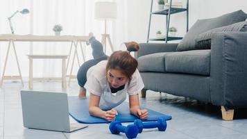 jonge dame in sportkleding oefeningen doet planken met gestrekt been en gebruikt laptop om thuis yoga video-tutorial te bekijken. afstandstraining met personal trainer, social distance. foto