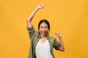 jonge aziatische dame met positieve uitdrukking, vrolijk en opwindend, gekleed in casual doek over gele achtergrond met lege ruimte. gelukkige schattige blije vrouw verheugt zich over succes. gezichtsuitdrukking concept. foto