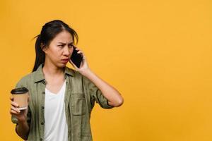 jonge aziatische dame praat via de telefoon en houdt koffiekopje met negatieve uitdrukking, opgewonden geschreeuw, huil emotioneel boos in casual doek en staat geïsoleerd op gele achtergrond. gezichtsuitdrukking concept. foto