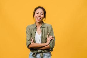 portret van jonge Aziatische dame met positieve uitdrukking, armen gekruist, breed glimlachen, gekleed in casual kleding en camera kijken over gele achtergrond. gelukkige schattige blije vrouw verheugt zich over succes. foto