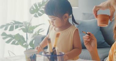 gelukkige vrolijke azië familie moeder leert peuter meisje verf keramische pot plezier ontspannen op tafel in de woonkamer thuis. tijd samen doorbrengen, sociale afstand, quarantaine voor coronaviruspreventie. foto