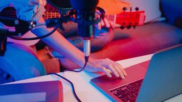 gelukkig Azië meisje blogger gitaar spelen en microfoon gebruiken zingen lied opnemen muziek sound mixer op laptop in moderne woonkamer thuisstudio 's nachts. maker van muziekinhoud, zelfstudie, uitzendconcept. foto
