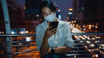 jonge azië zakenvrouw in mode kleding met gezichtsmasker met behulp van smartphone sms-bericht te typen terwijl je 's nachts buiten in de stedelijke stad staat. sociale afstand om verspreiding van het covid-19-concept te voorkomen. foto