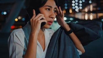 ernstig ontevreden, overstuur jonge Aziatische zakenvrouw die via de telefoon praat terwijl ze alleen buiten loopt in de stedelijke stadsnacht. zaken onderweg, sociale afstand om verspreiding van het covid-19-concept te voorkomen. foto