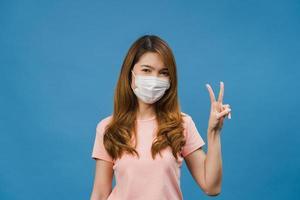 jong Azië meisje met medisch gezichtsmasker met vredesteken, aanmoedigen met gekleed in casual doek en kijken naar camera geïsoleerd op blauwe achtergrond. sociale afstand, quarantaine voor het coronavirus. foto