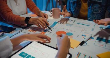 millennial azië mensen ontmoeten brainstormideeën over nieuw papierwerk projectcollega's die samenwerken plannen successtrategie genieten van teamwork in een klein modern nachtkantoor. collega teamwerk concept. foto