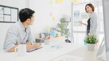 Aziatische zakenmensen ontmoeten brainstormen uitvoeren van zakelijke presentatie-ideeën projectcollega's en dragen een beschermend gezichtsmasker terug in een nieuw normaal kantoor. levensstijl en werk na het coronavirus. foto