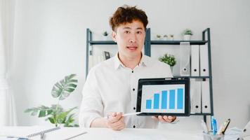 azië zakenman sociale afstand in nieuwe normale situatie voor viruspreventie kijkend naar camera met tabletpresentatie aan collega over plan in videogesprek terwijl u op kantoor werkt. foto