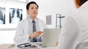 serieuze azië mannelijke arts in wit medisch uniform met behulp van computer laptop levert geweldig nieuws praten resultaten of symptomen bespreken met vrouwelijke patiënt zitten aan bureau in gezondheidskliniek of ziekenhuiskantoor. foto