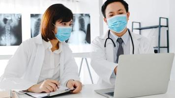 medisch team van azië serieuze mannelijke en jonge vrouwelijke arts met beschermende gezichtsmaskers die computertomografie bespreken in het ziekenhuiskantoor. sociale afstand, levensstijl nieuw normaal na corona virus. foto
