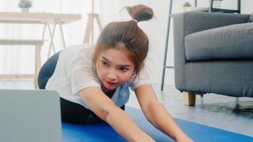 jonge Koreaanse dame in sportkledingoefeningen die aan het trainen zijn en laptop gebruiken om thuis yoga-videotutorials te bekijken. afstandstraining met personal trainer, sociale afstand, online onderwijsconcept. foto
