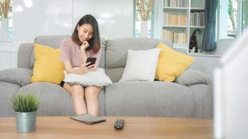 jonge aziatische vrouw die smartphone gebruikt die sociale media controleert, voelt zich gelukkig lachend terwijl ze op de bank ligt wanneer ze thuis in de woonkamer ontspant. levensstijl Latijnse en Spaanse etniciteit vrouwen bij huis concept. foto