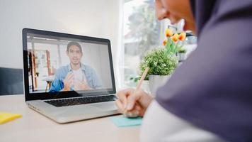 azië moslim zakenvrouw met behulp van laptop praten met collega over plan door video-oproep brainstorm online vergadering terwijl op afstand werken vanuit huis in de woonkamer. social distancing, quarantaine voor corona virus foto
