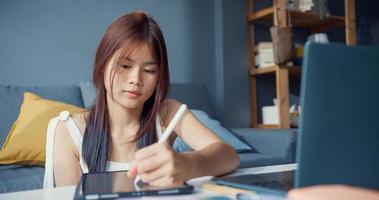 jonge Aziatische meisje tiener met casual gebruik computer laptop focus om online te leren schrijven lezing in digitale laptop in de woonkamer thuis. isoleer onderwijs online e-learning coronavirus pandemie concept. foto