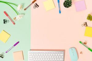 minimale werkruimte - creatieve platliggende foto van werkruimtebureau. bovenaanzicht bureau met toetsenbord, muis en zelfklevende notitie op pastel groen roze kleur achtergrond. bovenaanzicht met kopie ruimtefotografie.