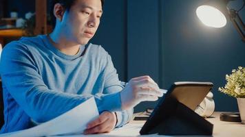 azië freelance zakenman focus werk pen schrijven op tabletcomputer bezig met vol grafiekpapier op bureau in woonkamer thuis overuren 's nachts, thuiswerken tijdens covid-19 pandemie concept. foto
