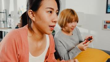 lesbische lgbtq-vrouwen spelen thuis een videogame. jonge Aziatische dame met behulp van draadloze controller met grappig gelukkig moment samen op de bank in de woonkamer. ze hebben een geweldige en leuke tijd om vakantie te vieren. foto