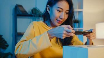 jonge aziatische vrouw gebruikt smartphone en neemt barcodefoto op pakketproduct voor verzending naar de klant in het thuiskantoor 's nachts. klein bedrijf, online marktlevering, lifestyle freelance concept. foto