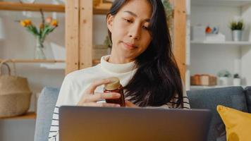 zieke jonge aziatische vrouw houdt medicijnen vast en zit op de bank videogesprek met laptop overleg met arts thuis. meisje neemt medicijnen in na doktersbevel, quarantaine thuis, social distancing coronavirus concept. foto