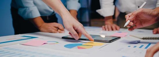 Azië zakenlieden en zakenvrouwen ontmoeten brainstormen ideeën collega's die samenwerken bij het plannen van successtrategie genieten van teamwork in nachtkantoor. panoramische bannerachtergrond met exemplaarruimte. foto