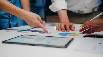 millennial azië zakenlieden en zakenvrouwen die brainstormen over ideeën over nieuwe papierwerkprojectcollega's die samenwerken bij het plannen van successtrategie genieten van teamwork in een klein modern nachtkantoor. foto