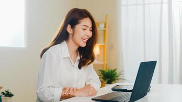 jonge Aziatische zakenvrouw die laptop videogesprek gebruikt om met een paar te praten terwijl ze vanuit huis in de woonkamer werkt. zelfisolatie, sociale afstand, quarantaine voor coronavirus in het volgende normale concept. foto