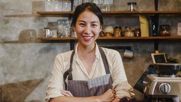 portret jonge aziatische vrouw barista gelukkig lachend in stedelijk café. eigenaar van een klein bedrijf Indonesisch meisje in schort ontspannen brede glimlach op zoek naar camera aan de balie in de coffeeshop. foto