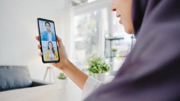 jonge azië moslim zakenvrouw met behulp van slimme telefoon praten met collega door videochat brainstorm online vergadering terwijl op afstand werken vanuit huis in de woonkamer. sociale afstand, quarantaine voor het coronavirus. foto