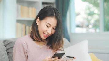 jonge glimlachende aziatische vrouw die smartphone gebruikt om online winkelen met een creditcard te kopen terwijl ze op de bank ligt wanneer ze thuis in de woonkamer ontspant. levensstijl Latijnse en Spaanse etniciteit vrouwen bij huis concept. foto