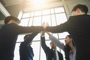 Aziatische zakenmensen die hun handen in elkaar slaan. foto