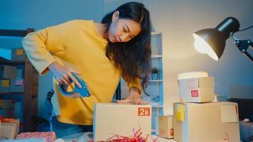 jonge azië zakenvrouw bereiden product gebruik tape verpakkingsdoos voor verzending naar klant inkooporder in thuiskantoor 's nachts. eigenaar van een klein bedrijf, online marktlevering, lifestyle freelance concept. foto
