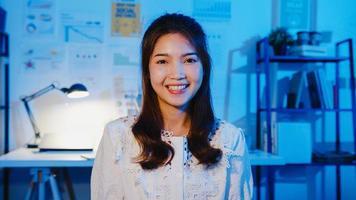 portret van mooie zakenvrouw slimme vrijetijdskleding kijken naar de camera en glimlachen, gelukkig in moderne kantoor werkplek nacht. jonge aziatische dame praat met collega in videogesprek thuis. foto