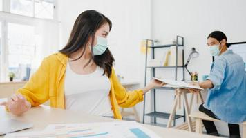 Aziatische zakenmensen dragen een gezichtsmasker voor sociale afstand in een nieuwe normale situatie voor viruspreventie en het doorgeven van documenten met afstand houden op kantoor. levensstijl en werk na het coronavirus. foto