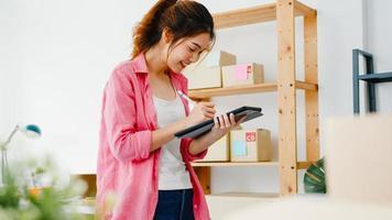 jonge azië ondernemer zakenvrouw check product inkooporder op voorraad en opslaan op tablet computer werk thuis kantoor. eigenaar van een klein bedrijf, online marktlevering, lifestyle freelance concept. foto