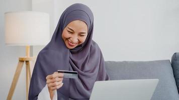 azië moslimdame met behulp van laptop, creditcard kopen en kopen e-commerce internet in de woonkamer thuis. thuis blijven, online winkelen, zelfisolatie, sociale afstand, quarantaine voor coronavirus. foto