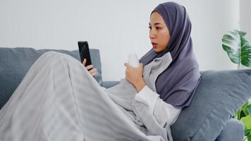 jonge azische moslimdame draagt hijab met behulp van een telefoonvideogesprek met een doktersconsultatie of online consultatie op de bank in de woonkamer thuis. sociale afstand, quarantaine voor coronavirusconcept. foto