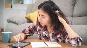 Aziatische studentenvrouw doet thuis huiswerk, vrouw drinkt koffie en gebruikt een tablet om thuis op de bank in de woonkamer te zoeken. levensstijl vrouwen ontspannen thuis concept. foto