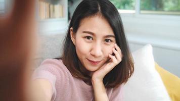 jonge aziatische tiener vrouw vlog thuis, vrouw gebruikt smartphone die vlog video maakt naar sociale media in de woonkamer. levensstijl vrouw ontspannen in de ochtend thuis concept. foto
