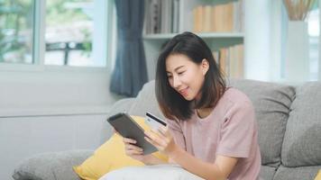 jonge glimlachende aziatische vrouw die tablet gebruikt om online winkelen met een creditcard te kopen terwijl ze op de bank ligt wanneer ze thuis in de woonkamer ontspant. levensstijl Latijnse en Spaanse etniciteit vrouwen bij huis concept. foto