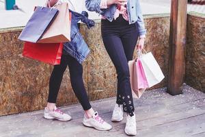 twee jonge vrouw die boodschappentassen draagt terwijl ze over straat loopt na een bezoek aan de winkels foto